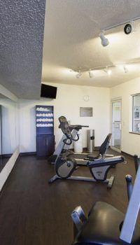 Фактурно оштукатуренный двухуровневый потолок, освещаемый спотами, и фальшь окно на стене, придают залу больший объём