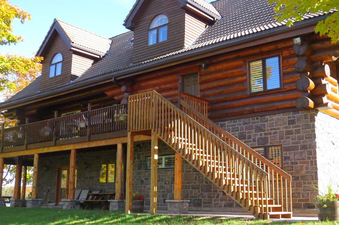 Дом из бревна с цокольным этажом, выполненным в наземном варианте