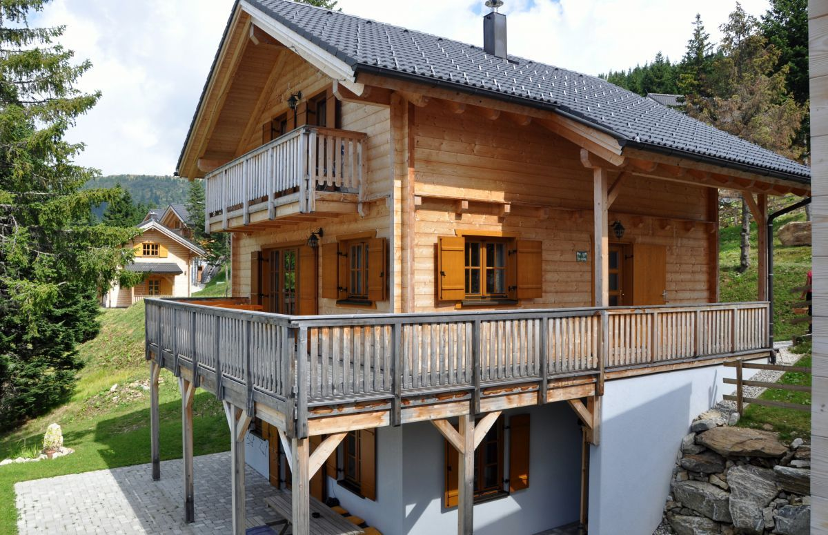 Дом из профилированного бруса с цокольным этажом на склоне: с одной стороны цоколь заглублён по всей высоте, а с другой полностью открыт